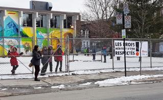 La banderole ne cache pas la belle murale de l'école au Pied-de-la-montagne, pavillon Saint-Jean-Baptiste.